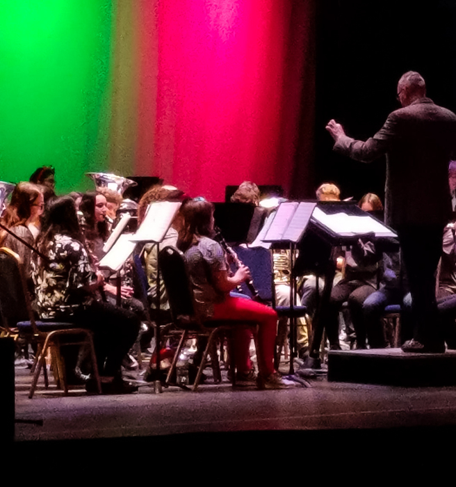 Voices Strong Choir Bands perform on stage at the Oroville State Theatre with students on stage and dramatic green and red backdrop