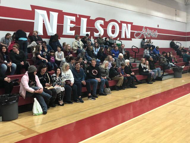 National History Day crowd sits on bleachers at Nelson Avenue Middle School