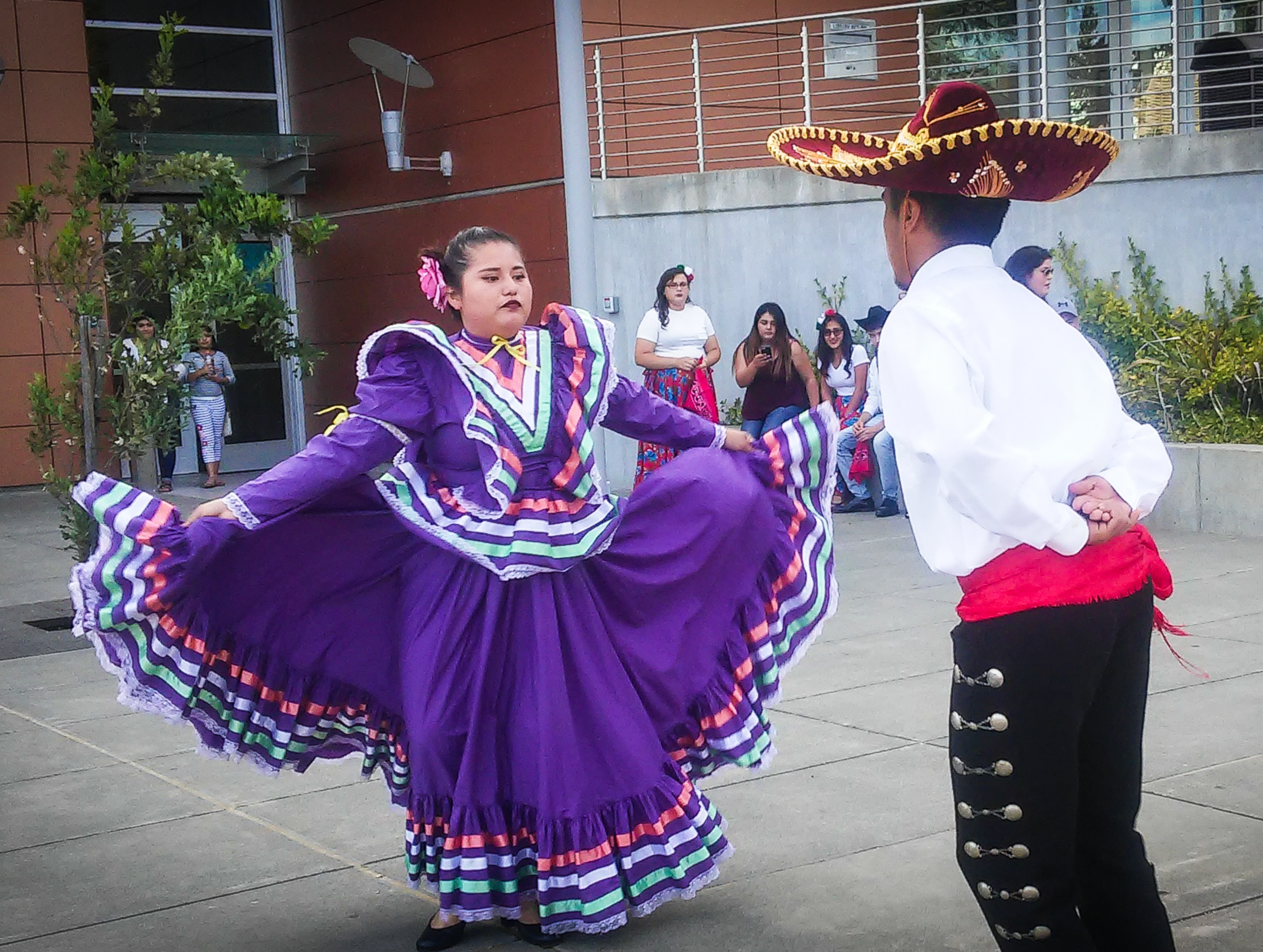 Women in traditional Mexican dress, purple and flowing, dancing with a man with sombrero, white shirt, black pants and red mid-sash