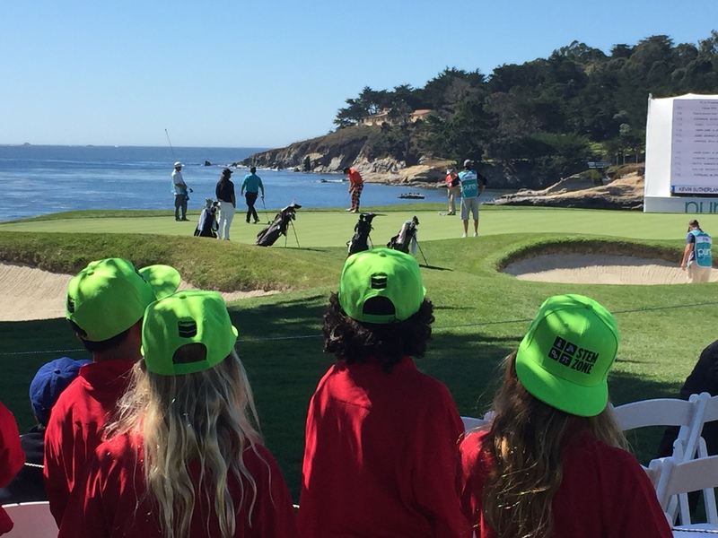 Students watch as golf pros move from location to take their shot