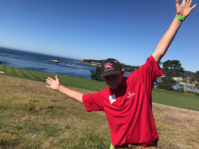 Picture of student posing with hands up in front of golf course and ocean background