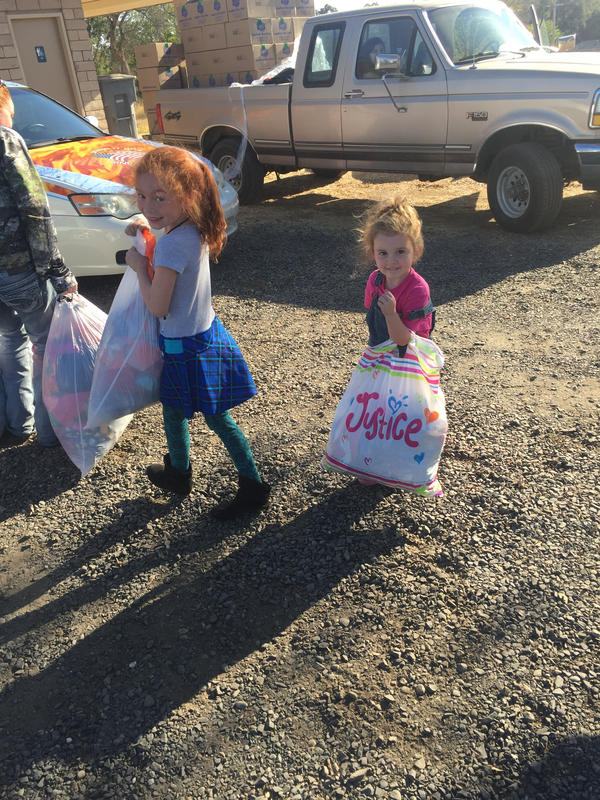 Two young girls helping by donating some of their belongings to Bangor community