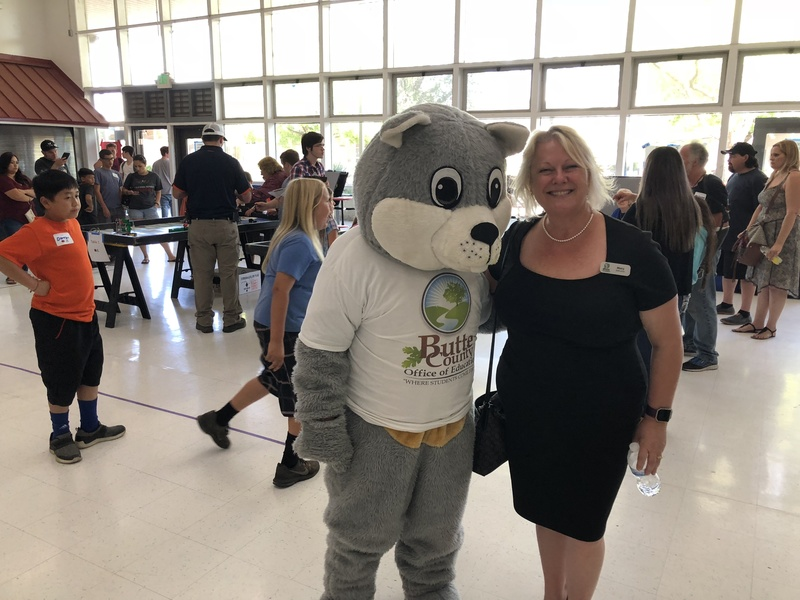 Photo of BCOE mascot Chewy the Squirrel with Deputy Superintendent Mary Sakuma with event festivities in the background.