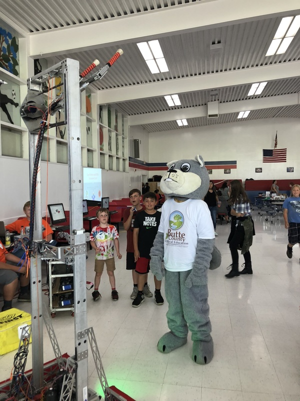 Photo of Chewy the Squirrel checking out the High School Robotics team's robot!