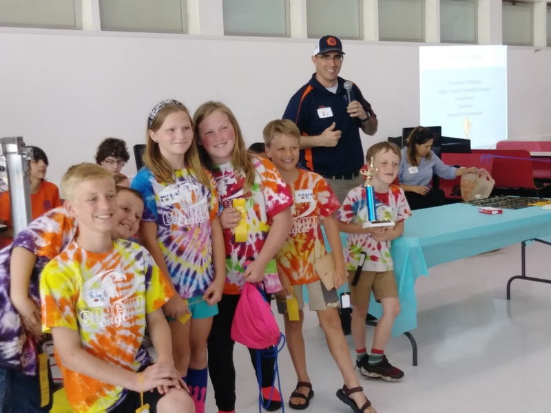 Photo of six children in tie dye shirts smiling with Butte Built Bots Founder Jon Andrew.