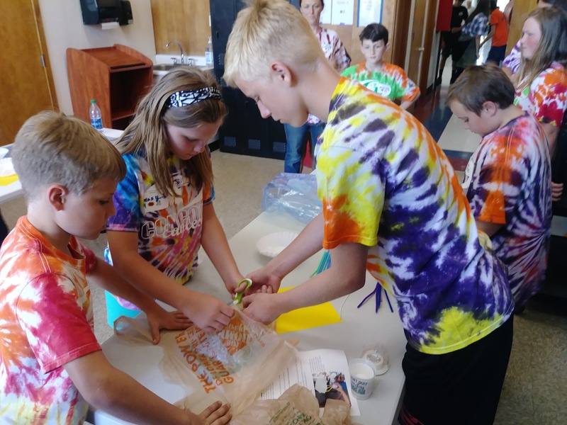 Photo of three students cutting a plastic bag together as part of their project.