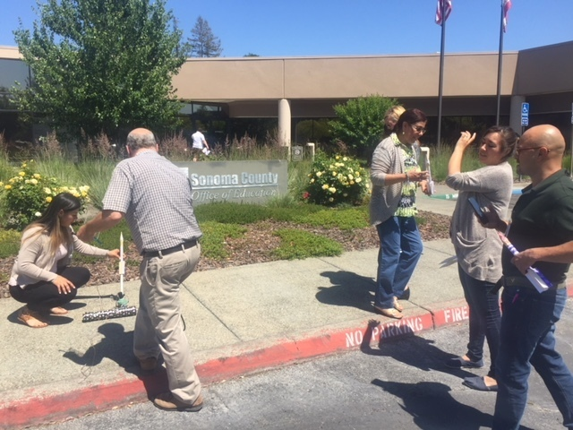 Sonoma County Office of Education building in background with five people on sidewalk about to launch a rocket that they made