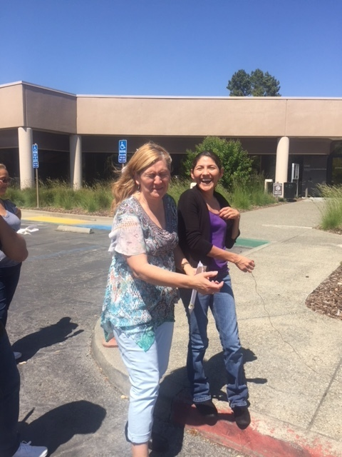 Sonoma County Office of Education building in background with two ladies on sidewalk holding remote control wire, one laughing, one grimaced with eyes shut in anticipation of launch, about to launch a rocket that they made